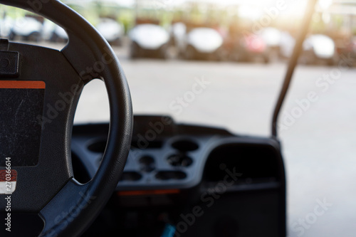 The steering wheel of a golf cart with blurred background many golf carts. - 270366614