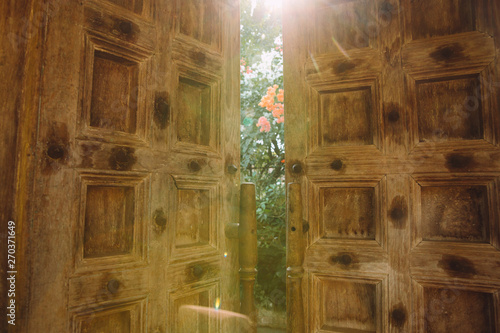 Photo Sunlight coming out through the wooden doors ajar on Goa