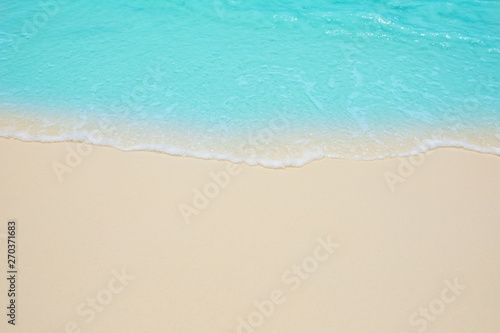 Photo Stands Turquoise Soft waves of blue sea on the Maldives beach for the background.