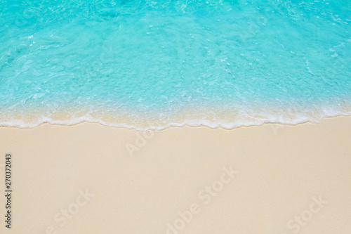 Soft waves of blue sea on the Maldives beach for the background.