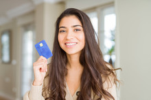 Young Woman Holding Credit Card As Payment With A Happy Face Standing And Smiling With A Confident Smile Showing Teeth