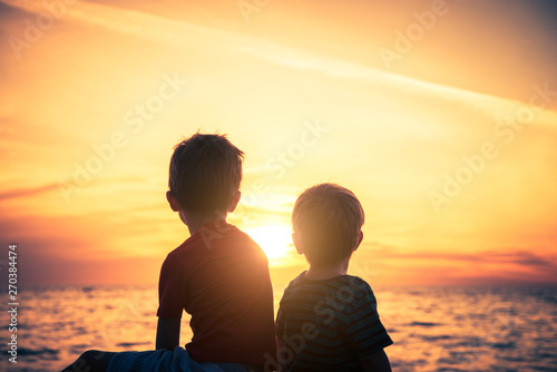 fototapeta na ścianę Two boys sitting on the rock at the beach at sunset