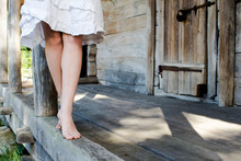 Legs Of A Girl In A White Dress, Stand On Socks On The Edge Of A Wooden Veranda