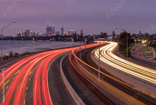 Winding Freeway at Night with Light Trails and City in background