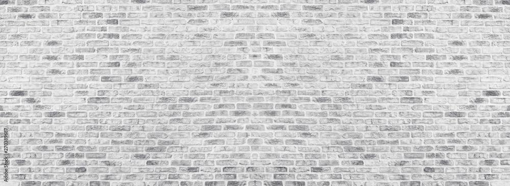 Wide white washed brick wall texture. Rough light gray brickwork. Whitewashed panoramic vintage background