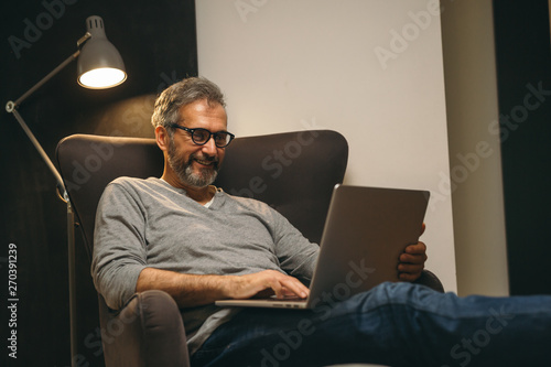 Tela  middle aged man using laptop relaxed in sofa in his home