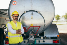 Worker Standing Crossed In Front Of Water Truck Tank