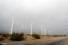 Windmills In A Dessert With Rain Drops On A Car Window.