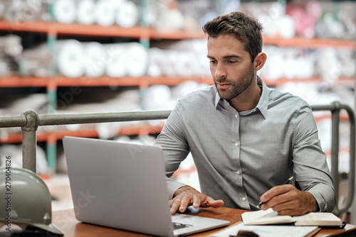 Photo  Warehouse manager taking notes and checking orders with a laptop