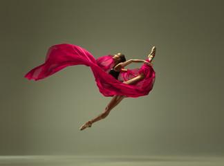Graciozna plesačica baleta ili klasična balerina plešu izolirane na sivoj pozadini studija. Žena s ružičastom svilenom tkaninom. Koncept plesa, gracije, umjetnika, suvremenog, pokreta, akcije i pokreta.