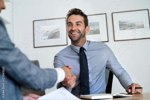 Fotografía  Manager sitting at his desk shaking hands with an employee