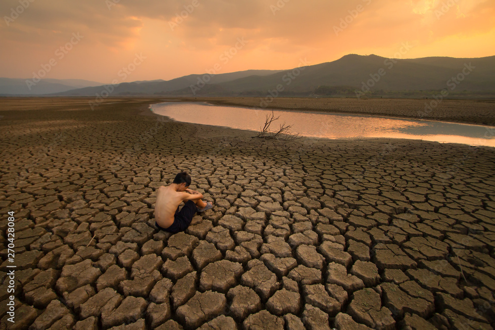 Fototapety, obrazy: Water crisis, Sad Children sitting on cracked earth near drying water at the river metaphor climate change, Global warming, Environment pollution.