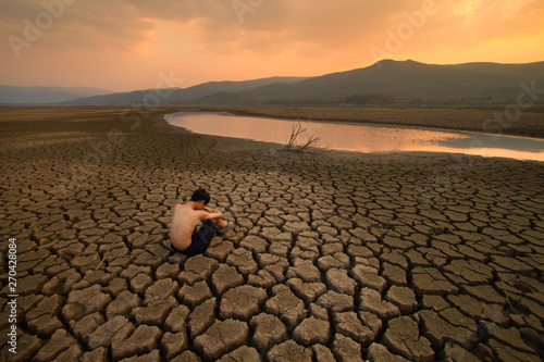 Fototapeta Water crisis, Sad Children sitting on cracked earth near drying water at the river metaphor climate change, Global warming, Environment pollution. obraz