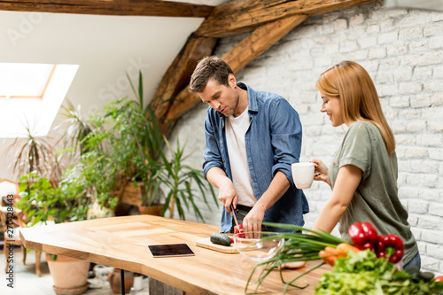 Photo sur Toile Les Textures Lovely cheerful young couple cooking dinner together