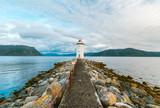 Biała latarnia morska na kamienistej skalnej wyspie o zachodzie słońca.
