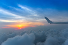 Wing Of The Air Plane On The Sea Of Cloud Sunset Sky Background From Window Airplane