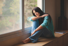 Woman Sitting On The Window Sill