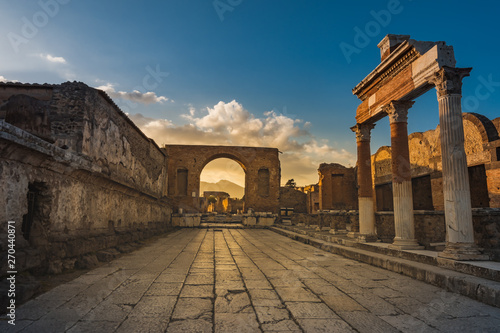 Ruins of ancient city of Pompeii, ancient roman city against Vesuvius volcano at sunset, Italy Fototapeta