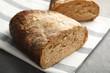 Leinwandbild Motiv Cut loaf of bread on grey table, closeup