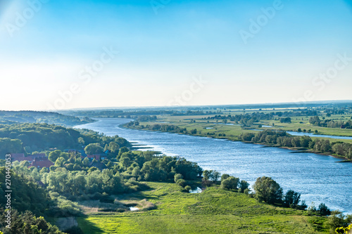 Fototapeta View over the Elbauen in Lower Saxony, Germany. You see a landscape with fields, meadows and the river Elbe under a blue sky. obraz