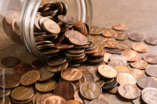 Pinturas sobre lienzo  Glass jar with coins on table, closeup. Money saving concept
