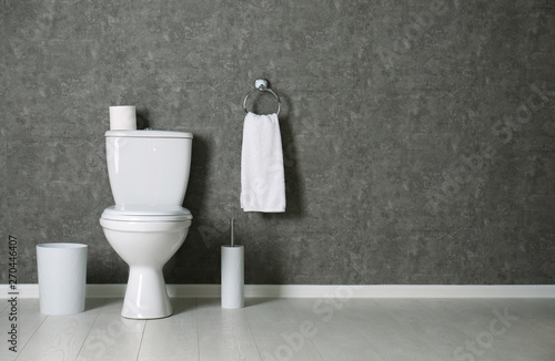 Simple bathroom interior with new toilet bowl near grey wall Canvas Print