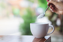 Unhealthy Woman Hand Holding Spoon Pouring Sugar In To Coffee Cup