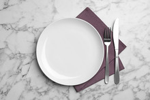 Stylish Ceramic Plate, Napkin And Cutlery On Marble Background, Flat Lay
