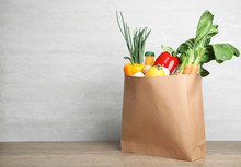 Paper Bag With Vegetables And Bottle Of Juice On Table Against Grey Background. Space For Text