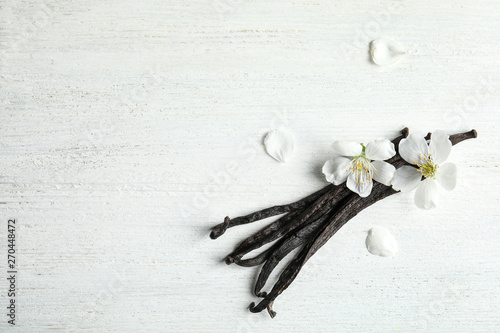 Fotomural  Flat lay composition with aromatic vanilla sticks and flowers on wooden backgrou