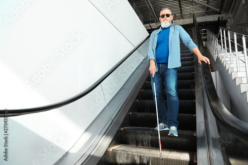 Photo Blind person with long cane on escalator indoors. Space for text
