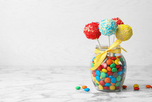 Yummy Bright Cake Pops In Glass Jar Full Of Candies On Table. Space For Text
