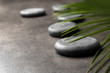 Spa stones and green leaf on grey background. Space for text