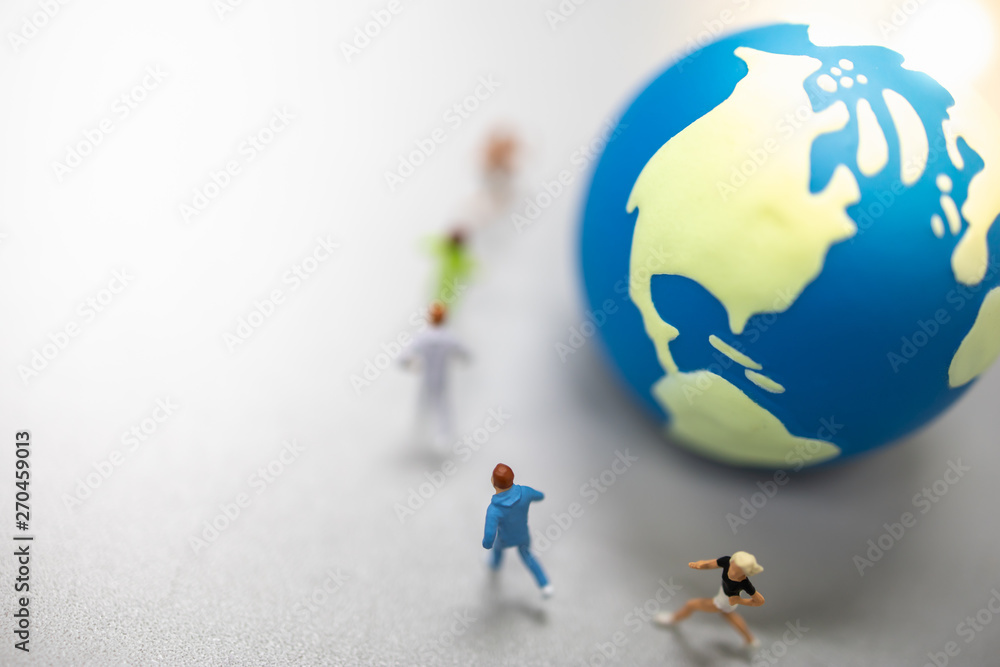 Fototapety, obrazy: Global Sport Concept. Close up of group of runner miniature figures running around mini world ball on ground with copy space.