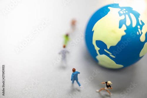 Global Sport Concept. Close up of group of runner miniature figures running around mini world ball on ground with copy space.