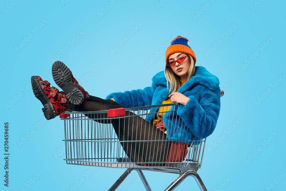 Confident weird female in shopping trolley - obrazy, fototapety, plakaty