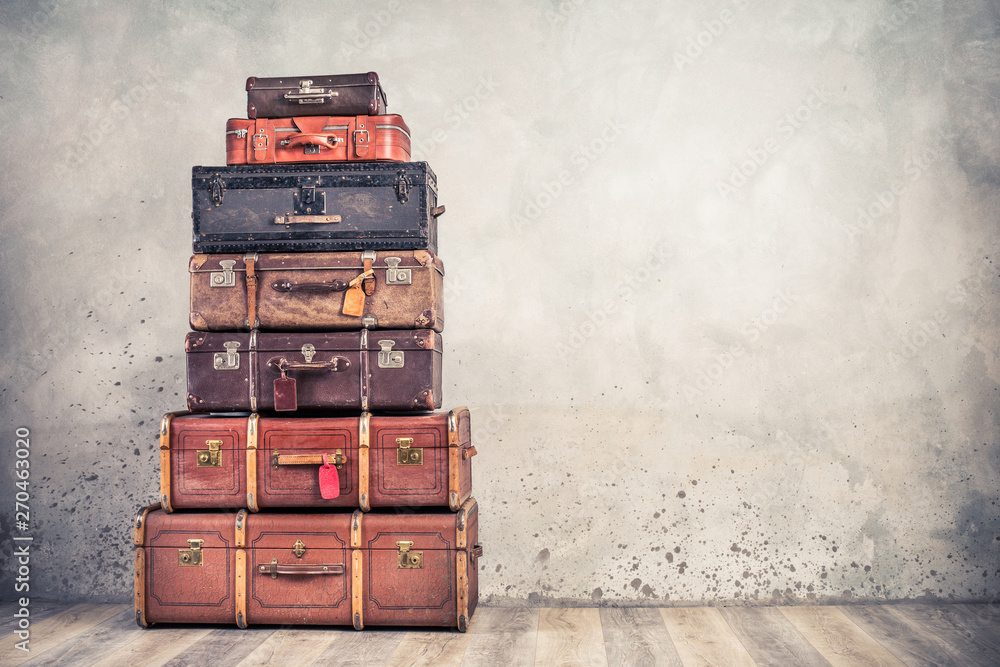 Fototapeta Vintage classic outdated trunks luggage with tags, old antique leather suitcases tower front concrete wall background. Travel baggage concept. Retro style filtered photo