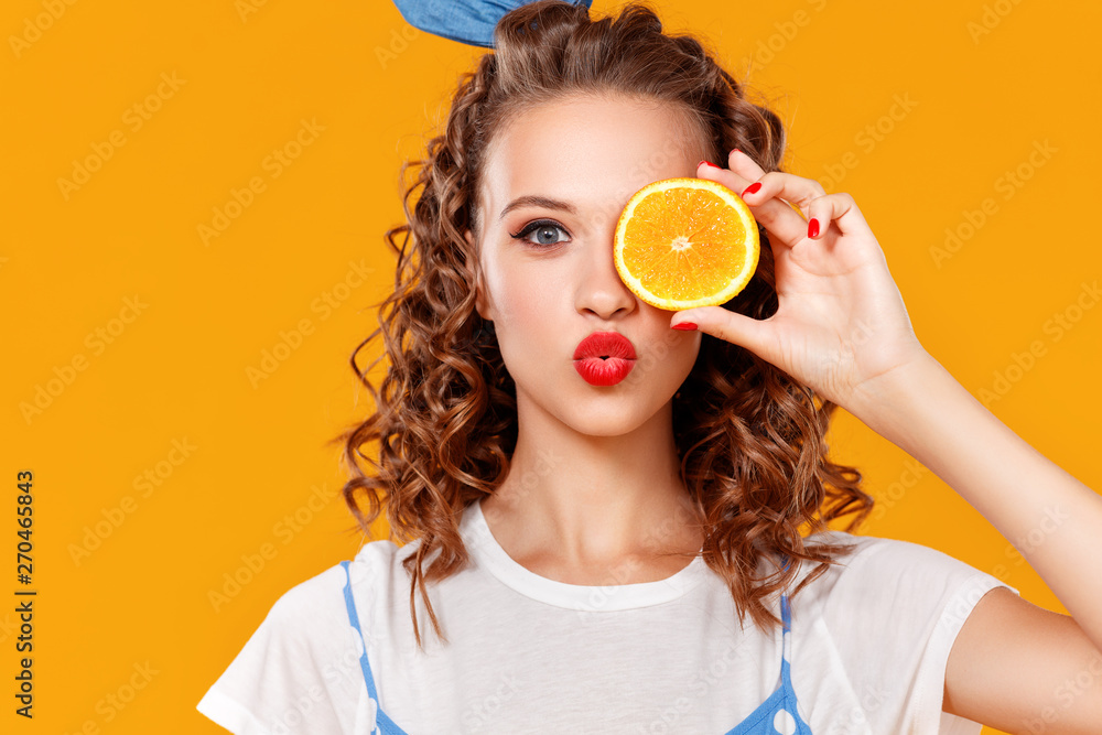 Fototapety, obrazy: cheerful young curly woman girl with   orange   on  yellow   background.
