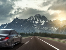 Car Drives Fast On The Highway Against The Backdrop Of A Mountain Range.