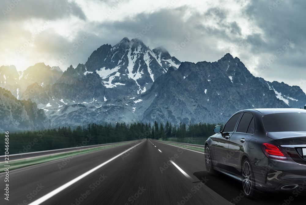 Fototapety, obrazy: Car drives fast on the highway against the backdrop of a mountain range.