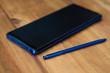 Blau-schwarzes Smartphone mit Stift zur Digitaleingabe auf Holzuntergrund