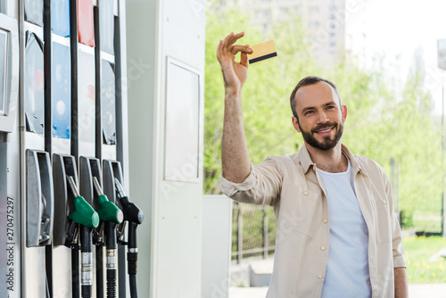 Photo  happy bearded man holding credit card and smiling at gas station