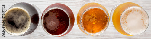 Photo Assorted beers on a white wooden surface, top view