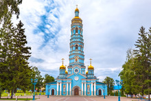 Light Blue High Church With Golden Domes Surrounded By Green Trees Under Large Rain Clouds On The Square. Cathedral Of The Nativity Of The Virgin, Ufa, Bashkortostan, Russia