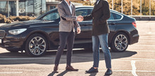 Photo Of Two Smart Elegant Men, Which Have A Deal About Car. They Are Doing Handshake.