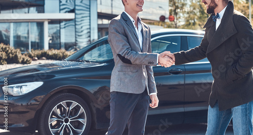 Fotografía  Photo of two smart elegant men, which have a deal about car