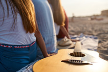 Isolated Photo Of Wooden Acoustic Guitar On Beach Towel. Back View Of Group Of Friends Sitting Together On White Sand Shore And Enjoying A Warm Sunset Above The Sea. Summer Playlist Concept.