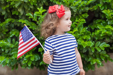 Adorable Little Girl Holding American Flag Outdoors On Beautiful Summer Day. Independence Day Concept. Patriotic Holiday. 4th Of July Party