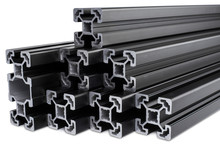 Stack Of Black Anodized Aluminum Extrusion Bars, Isolated White Background. Construction Metal Steel Factory Concept.