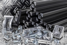 Stack Of Black Anodized Aluminum Extrusion Bars, Connector, Joint, Screw , Slot Nut And Angle Bracket Silver Shiny Diamond Plate Background. Construction Metal Steel Factory Concept.